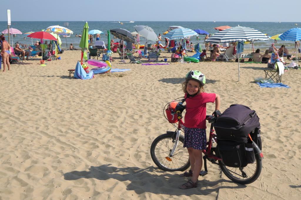 Malá cyklistka na pláži.