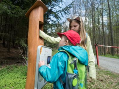 Děti u informační cedule Sluneční stezky ve Křtinách.