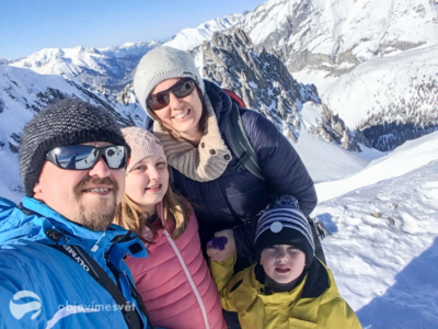Rodina v barevných bundách na horách.